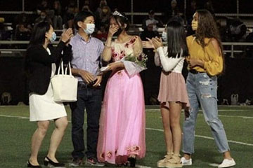 Senior Minh Ngo and her family celebrate her crowning as Homecoming Queen at halftime of the varsity football game Friday, October 2. The Hornets went on to beat the Lee's Summit Tigers, 36-20.